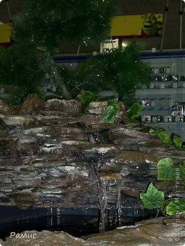 Водопад с разноцветными рыбками в большом магазине бытовой техники.  фото 2