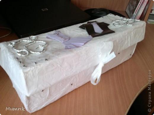 """Решили сделать сотруднице нашего отдела оригинальный подарок по случаю свадьбы. Много чего думали, но девушка сама настояла на бональном подарке - """"деньги"""". Просто дарить конверт - как-то не интересно.  И вот у меня родилась идея. Решила сделать праздничную коробочку. Обычную коробку из под обуви заклеила белой бумагой. Заклеивала обычным клеем сваренным из крахмала (первоначально с клеем переборщила и коробку слегка повело). По верх белой бумаги обклеила коробку тоненькой бумагой (в эту бумагу обувь заворачивают и кладут в коробки. Вот из коробок с обувью я эту бумагу и набрала). Клеила тонкую бумагу на уже ПВА. Клеила точечно, чтобы создавался эффект помятости. Потом из фольги накрутила сердечек и уголки (насмотрелась на этом сайте работ из фольги - ну оч понравились). По техники оригами собрала платье и рубашечку. Подмазала блестками. Т.к. бумага оч тонкая, клей ПВА был оч виден желтыми пятнами. Пришлось взять перламутровую гуашь и подкрасить немного. Потом на крышку и по всей коробке россыпью наклеила немного страз. фото 3"""