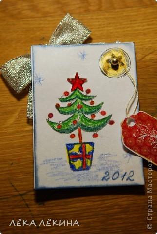"""С чем у вас ассоциируется детсво и Новый год? У кого-то с мандаринами, у кого-то с елкой....у меня с конфетами Аленка....почему не знаю. Сейчас эти конфеты любят мои дети. Вот смотрела я на фантики из-под них и решила их """"увековечить"""":) Сделала всего 3 штуки, т.к. не уверена что у Аленки много поклонников. Карточка двухсторонняя, на лицевой стороне на фоне белого атласа, блескучий олень, шарик с лицом Аленки (он двигается и тонирован золотом) и серебристый бантик...ну и снежинки, бусинки...вторая сторана полностью сделана вручную, новогодний мотивчик нарисован акварельными карандашами, плюс тонировка, печать Деда мороза, золотая патина и т.д. Мои коодинаты написаны на маленьком теге:) Кредиторов у меня нет, поэтому милости прошу, всех поклонников Аленки фото 3"""