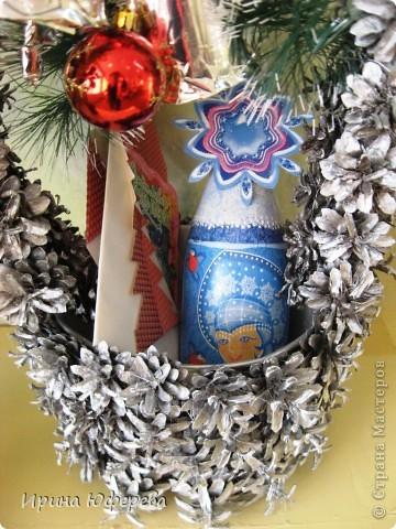 В прошлый раз мы показывали деревья из шишек, а сегодня у нас новогодняя корзинка. В основе бумажное ведерко от попкорна. Ручка из проволоки и картона. Всё оклеили шишками и покрыли аэрозолью. Колокольчики сделаны из стаканчиков от йогурта. Бутылочку и открытку смотрите в предыдущих работах https://stranamasterov.ru/node/142151 , потом здесь: https://stranamasterov.ru/node/129013 и здесь: https://stranamasterov.ru/node/123287.  Вот такой набор получился, дети просто в восторге! фото 2