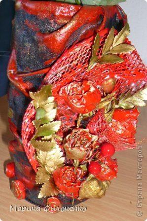 Здравствуйте, дорогие мастерицы! Идея в голову пришла быстро, когда под рукой не оказалось свободной вазы, а из под молока освободилась пластиковая бутылочка. Обклеила ее материалом, покрасила, а затем украсила упаковкой от цветов (сеточкой), покрашенными сухоцветами и речными камнями.  фото 2