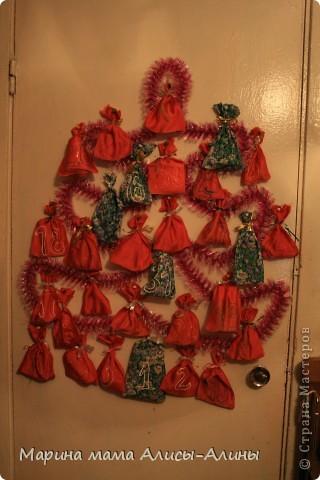 Решила дочке сделать адвент-календарь к новому году.До первого числа было всего пара дней,а хотелось сделать календарь на весь месяц.Сшила по быстрому мешочки.К сожалению красного матерьяла не хватило,дошила из того что нашла. Цифры написала контуром.Купила подарочки:мыльные пузыри,наклейки,магнитик-дракона,маленький шарик со снегом,красивые камешки для аквариума(будут для неё как сокровища), жвачки,конфеты и т.д.Сделала ёлку из мишуры и вразброс пришпилила мешочки.Сегодня утром открыли первый!Алисочке моей очень понравилось.Она с нетерпением ждала утра и вот свершилось!!!! фото 1