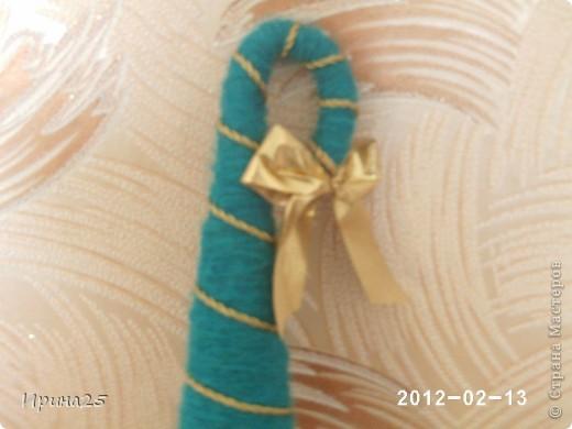 Вот она моя ёлочка.Выкладываю правда поздно,но может кому-нибудь на следующий год пригодится.Сделана из картонного конуса, обмотана (и кое-где подклеина) зелёной пряжей.Для украшения:золотая верёвочка(не знаю как правильно называется, но она во всех тканевыз магазинах продаётся)  намотанная как гирлянда и 2 бантика из золотой ткани.Горшочек-баночка от крема, обтянутая тканью, ствол-это палочка от мороженого обмотанная коричневой пряжей. Ну вот и всё, из ненужного  сварганила ёлочку. фото 2