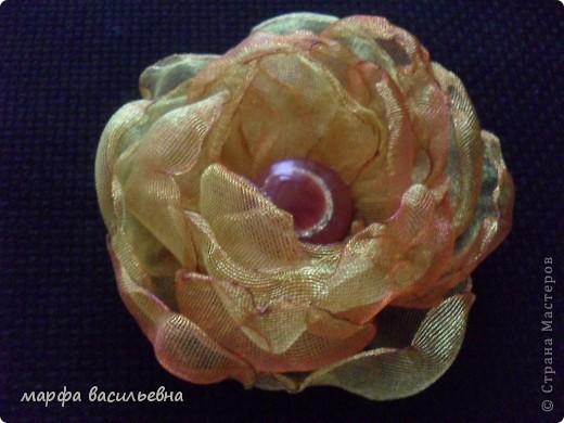Когда вечером есть время,можно сделать красивый цветок.Все просто,вырезаем из органзы лепестки разных размеров,опаливаем над свечкой срезы,потом все лепестки сшиваем,в центр пришиваем что-нибудь и получается кое-что. фото 3