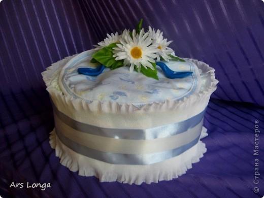 """Торт для мальчика, но его можно """"испечь"""" в цвете и для девочки:) Ингредиенты: памперсы 24шт., слюнявчик, посуда детская (вилочка и ложечка для кормления), декоративные цветы и лента. Размер: 23х17см."""