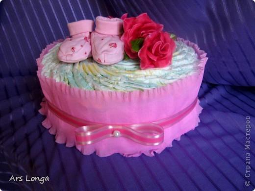 Тортик для девочки. Ингредиенты: памперсы 36шт., пинетки, декоративные цветы и ленты, гофробумага. Размер: 23х17см.
