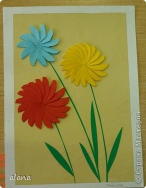На сей раз открыточка с объемными цветами. Для начала продумываем цвет. Сложив полоску бумаги, вырезаем лепесток. Заготовив достаточное количество, складываем каждый лепесток пополам (вдоль). И отметив на бумаге центр цветка, начинаем приклеивать лепестки, смазывая клеем только половинку его. Следующий лепесток приклеиваем, чуть заслоняя первый и т.д. фото 3