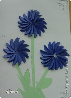 На сей раз открыточка с объемными цветами. Для начала продумываем цвет. Сложив полоску бумаги, вырезаем лепесток. Заготовив достаточное количество, складываем каждый лепесток пополам (вдоль). И отметив на бумаге центр цветка, начинаем приклеивать лепестки, смазывая клеем только половинку его. Следующий лепесток приклеиваем, чуть заслоняя первый и т.д. фото 5