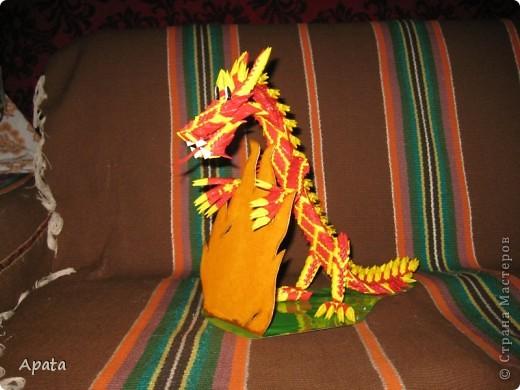 Дракон опирающийся на рамку для фотографии в форме костра. фото 1
