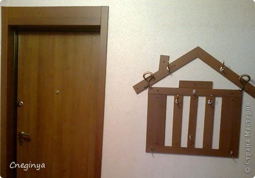 Муж сделал откосы на дверь в прихожую и, как часто бывает, остались кусочки, которые тут же у меня в голове превратились в композицию. Сделали домик.  Сперва все рассчитали и выпилили, сделали дырочки под крепления, потом собрали с обрадной стороны на сроительный степлер, это сделано для того, чтоб конструкция не развалилась при примерке на стену. Конечно, материала нам не хватило, и пришлось покупать ещё одну планку, так у нас получились кусочки разной ширины, что намного интересней! Далее все аккуратно повешали на стену, каждую планку на 2 дюбеля, и прикрепили крючки. фото 2