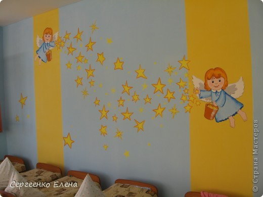 Наступило лето, а с ним и пора ремонтов в детском саду. Первой отремонтировали спальню у самых маленьких детей, в яслях. Воспитатели всё делали сами, а когда стены были готовы, пригласили мены для росписи стен. Ангелочка подсмотрели в одной из детских книжек. На первой фотографии самая большая стена, поэтому уместилось сразу два ангелочка, которые разбрасывают звёздочки счастья. Окна выходят на солнечную сторону, поэтому основной тон стен нежно-голубой, а элементы росписи (звёзды, ведёрко и волосы ) под цвет жалюзи. фото 1