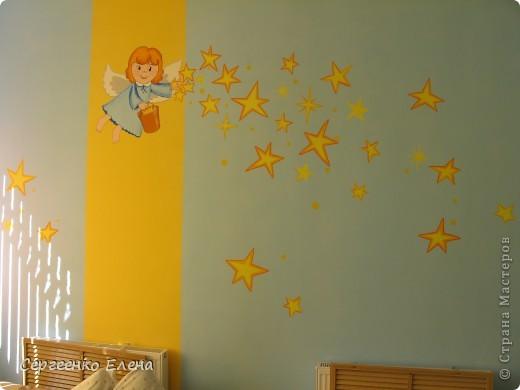Наступило лето, а с ним и пора ремонтов в детском саду. Первой отремонтировали спальню у самых маленьких детей, в яслях. Воспитатели всё делали сами, а когда стены были готовы, пригласили мены для росписи стен. Ангелочка подсмотрели в одной из детских книжек. На первой фотографии самая большая стена, поэтому уместилось сразу два ангелочка, которые разбрасывают звёздочки счастья. Окна выходят на солнечную сторону, поэтому основной тон стен нежно-голубой, а элементы росписи (звёзды, ведёрко и волосы ) под цвет жалюзи. фото 4