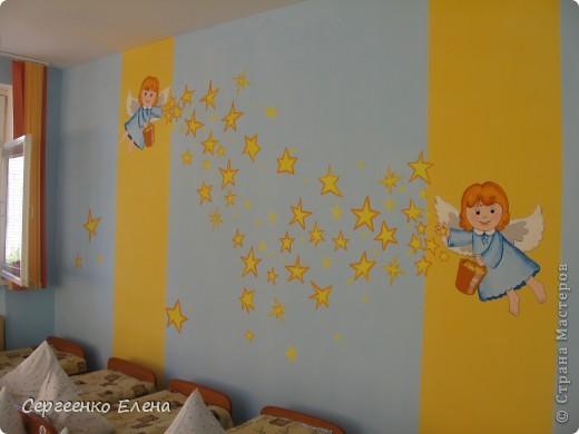 Наступило лето, а с ним и пора ремонтов в детском саду. Первой отремонтировали спальню у самых маленьких детей, в яслях. Воспитатели всё делали сами, а когда стены были готовы, пригласили мены для росписи стен. Ангелочка подсмотрели в одной из детских книжек. На первой фотографии самая большая стена, поэтому уместилось сразу два ангелочка, которые разбрасывают звёздочки счастья. Окна выходят на солнечную сторону, поэтому основной тон стен нежно-голубой, а элементы росписи (звёзды, ведёрко и волосы ) под цвет жалюзи. фото 6