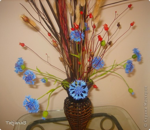 Композиция выполнена из цветов васильков из холодного фарфора и сухоцветов. Сухоцветы трава, колоски злаков и окрашенные коробочки настоящих васильков. фото 4