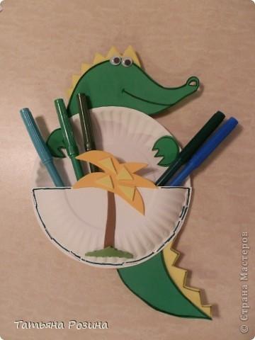 Вот такой крокодил-карманчик сделан из одноразовых бумажных тарелочек маленького размера. Аппликация сделана из картона. Все детали склеивались двусторонним  скотчем. что под силу малышу. Контуры, выполненные  черным фломастером  для  яркости, конечно, должен помочь сделать взрослый.  фото 1