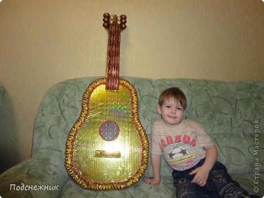 На этом фото только каркас гитары. Хотя преобладающая часть конфет уже приклеена. И мой сынишка (для демонстрации размера гитары) фото 1