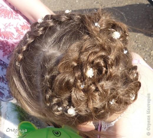 Общий вид. Прическа состоит из плетеных кос и цветов из волос, украшена декоративными шпильками. фото 1