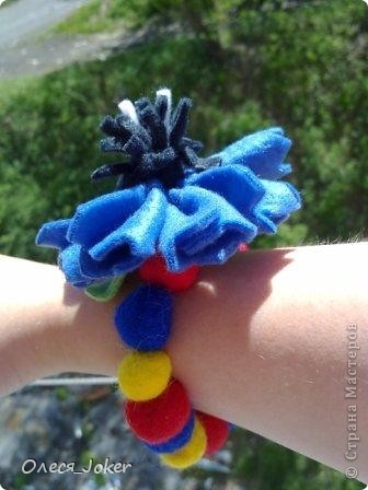 Решила поделиться МК по созданию такого браслета. Для браслета длиной 20 см нам потребуется: Шерсть для валяния красного, желтого и синего цвета (цвета можно выбирать любые) Вода, мыло Иголка, ножницы, полотенце, терка. Для цветка: 1 синий лоскут флиса, 1 зеленый, 1 белый, 1 черный. Нитки зеленые, черные.  Шпажка, клей, ножницы. Ну что ж, приступим. фото 1
