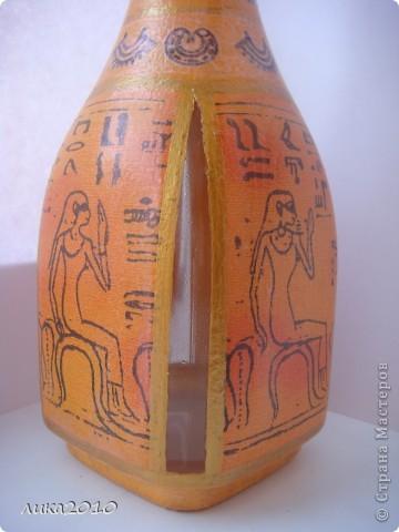 Принесли графинчик и попросили его приукрасить. В желто-оранжевой гамме с египетскими мотивами.Когда-то что-то подобное делала ( https://stranamasterov.ru/node/187113 ), но повторяться полностью не захотела да и форма другая...Салфетка, распечатка иероглифов, золотая краска, лак... Пробочку оклеила жатой салфеткой. На бочках оставила окошечки для контроля за жидкостью. фото 3