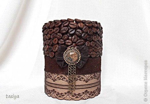 Свеча кофе с шоколадом. Трехслойная (посерёдке молотый кофе))))) Высота 12 см, диаметр 10 см. Идею с бантиком и висюльками подсмотрела у Этери http://stranamasterov.ru/user/137863  Свечи делаю из высококачественного парафина-свечного, у на он продаётся в плитах по 5 кг. Плавлю его вместе со стеарином в соотношении 1:5 (где 1 это стеарин). Плавлю на водяной бане. Заливаю в любую железную банку (ровную) подходящей формы, предварительно привязав на палочку фитиль (так, чтобы края палочки лежали на стенках банки) и опустив его в форму. Остывает свеча у меня в морозилке, около часа (зависит от объёма). Когда она остыла, возле фитилька образуется ложбинка, её можно залить остатками воска и добавить 5-10 капель эссенции. Чтобы извлечь свечу из банки, нужно опустить банку в кипяток на минутку, стенки свечи расплавятся и она легко достанется))) Далее клею зерна горячим пистолетом в 2 слоя, молотый кофе на ПВА, предварительно обезжирив нужную поверхность.Ну вроде как всё)))) фото 2