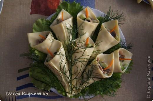 """Закуска """"Каллы"""" Рецепт очень прост: Вареное куриное феле, жареные шампиньоны и нарезаный кубиками огурец; все смешиваем и заправляем майонезом. Небольшую порцию получившегося """"салатика"""" (около столовой ложки) выкладываем на ломтик плавленого сыра и формируем цветок. Украшаем морковкой как на фото.  Лучше, чтоб каждый цветок лежал на отдельном листе салата. Когда я готовила эту закуску, было жарко, сыр начал плавиться, каллы слипались между собой. Не допускайте моих ошибок! А так получилось очень даже вкусно!   фото 1"""