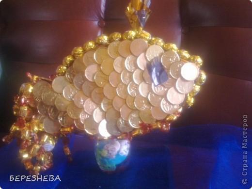 """В основу рибки вирізала пінопласт,потім загорнула в золоту фольгу,шоколадні монети клеїм гарячим клеєм в вигляді луски.Хвіст із """"Еклерів""""по краю """"Золота лілія"""",корона це фантик на зубочистці,очко(самоклейка),ротик бусини. фото 2"""