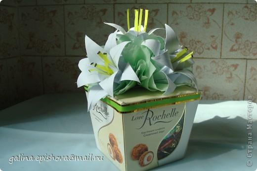 Вот так на скорую руку украсила коробочку с конфетами на день рожденья. Захотелось подарить не просто коробочку конфет, а конфеты с цветами. Лилии-оригами из квадратного листа делать и не сложно и не долго. У меня даже не было зеленой бумаги для листьев, заменила салфетками.  фото 1