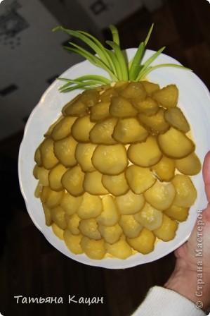 """Салат """"Ананас"""" Рецепт 1-й слой: картофель (отварной в мундире, потереть на терку) 2-й слой: лук (мелко нарезанный) 3-й слой: половина куриного мяса (отварить, мелко нарезать) 4-й слой: маринованные огурцы (нарезать кубиками) 5-й слой: оставшееся куриное мясо 6-й слой: сыр (натереть) 7-й слой: яйца (отварить, натереть) Выкладывать на овальное блюдо. Слои немного посолить, поперчить и смазать майонезом. Верхний слой салата хорошо смазать майонезом и украсить половинками грецких орехов и перьями зеленого лука.  * Вместо половинок грецких орехов поверхность салата можно густо посыпать рублеными грецкими орехами. Грецкие орехи можно заменить ломтиками консервированных шампиньонов, украсив ими поверхность салата в виде чешуек ананаса, выкладывая ломтики грибов немного внахлест или солеными (маринованными) огурчиками.  фото 2"""