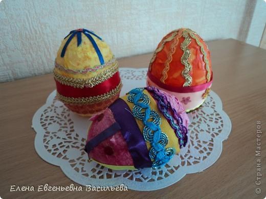 Эти пасхальные яйца мы изготовили на основе пластиковой формы. Две части яйца /внутри была игрушка-сюрприз/ плотно  приклеили друг к другу и объклеили бумажными салфетками всю поверхность заготовки. Когда салфетки высохли, декорировали яйцо тесьмой, кружевом, блестками, пуговицами, камушками и т.п. Каждый постарался проявить свою фантазию и творчество. Получились вот такие декоративные яйца к светлому празднику Пасхи. фото 1