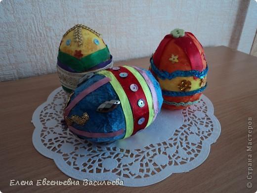 Эти пасхальные яйца мы изготовили на основе пластиковой формы. Две части яйца /внутри была игрушка-сюрприз/ плотно  приклеили друг к другу и объклеили бумажными салфетками всю поверхность заготовки. Когда салфетки высохли, декорировали яйцо тесьмой, кружевом, блестками, пуговицами, камушками и т.п. Каждый постарался проявить свою фантазию и творчество. Получились вот такие декоративные яйца к светлому празднику Пасхи. фото 2