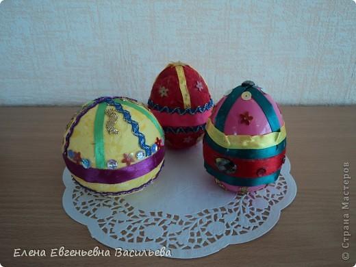 Эти пасхальные яйца мы изготовили на основе пластиковой формы. Две части яйца /внутри была игрушка-сюрприз/ плотно  приклеили друг к другу и объклеили бумажными салфетками всю поверхность заготовки. Когда салфетки высохли, декорировали яйцо тесьмой, кружевом, блестками, пуговицами, камушками и т.п. Каждый постарался проявить свою фантазию и творчество. Получились вот такие декоративные яйца к светлому празднику Пасхи. фото 3