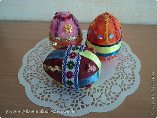 Эти пасхальные яйца мы изготовили на основе пластиковой формы. Две части яйца /внутри была игрушка-сюрприз/ плотно  приклеили друг к другу и объклеили бумажными салфетками всю поверхность заготовки. Когда салфетки высохли, декорировали яйцо тесьмой, кружевом, блестками, пуговицами, камушками и т.п. Каждый постарался проявить свою фантазию и творчество. Получились вот такие декоративные яйца к светлому празднику Пасхи. фото 4