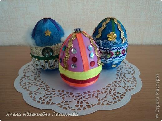 Эти пасхальные яйца мы изготовили на основе пластиковой формы. Две части яйца /внутри была игрушка-сюрприз/ плотно  приклеили друг к другу и объклеили бумажными салфетками всю поверхность заготовки. Когда салфетки высохли, декорировали яйцо тесьмой, кружевом, блестками, пуговицами, камушками и т.п. Каждый постарался проявить свою фантазию и творчество. Получились вот такие декоративные яйца к светлому празднику Пасхи. фото 5