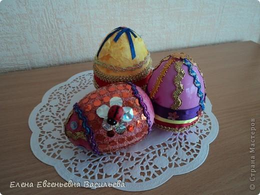 Эти пасхальные яйца мы изготовили на основе пластиковой формы. Две части яйца /внутри была игрушка-сюрприз/ плотно  приклеили друг к другу и объклеили бумажными салфетками всю поверхность заготовки. Когда салфетки высохли, декорировали яйцо тесьмой, кружевом, блестками, пуговицами, камушками и т.п. Каждый постарался проявить свою фантазию и творчество. Получились вот такие декоративные яйца к светлому празднику Пасхи. фото 6