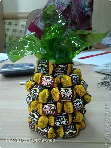 Давно любуюсь на букеты и фрукты  из конфет. Присмотрела идею- ананас из конфет для знакомой. Она большая любительница сладкого и фруктов. К тому же  большая мастерица выбирать ананасы. Подарок ей очень понравился. Внутри моего ананаса- сюрприз- красивый браслет.  Для изготовления я взяла маленькую пластиковую бутылку укоротила ее, внутрь поместила украшение, снаружи бутылку обклеила двухсторонним скотчем. И снизу вверх начала приклеивать конфеты. Для зелени обычно используется гофрированная бумага. У меня ее нет. Попробовала из пластиковой бутылки вырезать кусочки в виде листочков и подержать над огнем. Они сами очень быстро закручиваются, причем так быстро, что не успеваешь повлиять на их форму. Вот и получилась такая хаотичная зелень. фото 1