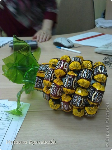 Давно любуюсь на букеты и фрукты  из конфет. Присмотрела идею- ананас из конфет для знакомой. Она большая любительница сладкого и фруктов. К тому же  большая мастерица выбирать ананасы. Подарок ей очень понравился. Внутри моего ананаса- сюрприз- красивый браслет.  Для изготовления я взяла маленькую пластиковую бутылку укоротила ее, внутрь поместила украшение, снаружи бутылку обклеила двухсторонним скотчем. И снизу вверх начала приклеивать конфеты. Для зелени обычно используется гофрированная бумага. У меня ее нет. Попробовала из пластиковой бутылки вырезать кусочки в виде листочков и подержать над огнем. Они сами очень быстро закручиваются, причем так быстро, что не успеваешь повлиять на их форму. Вот и получилась такая хаотичная зелень. фото 2