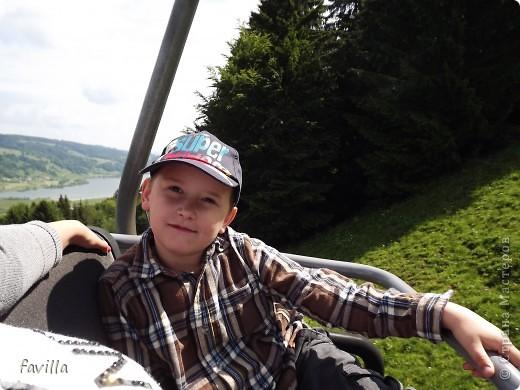 Alpsee Coaster самый длинный в Германии родельбан (горка для катания на санях) Длина 3 км, подъем в гору (на высоту около 1400 м) на подвесной дороге. При спуске - 68 поворотов, 23 волны, 7 прыжков, 4 моста, и 430-градусный спиральный поворот. Скорость развивается до 40 км в час Подъем в гору происходит на подвесной дороге.  Я фотографировала  маму и Вику со своего сиденья.  фото 5