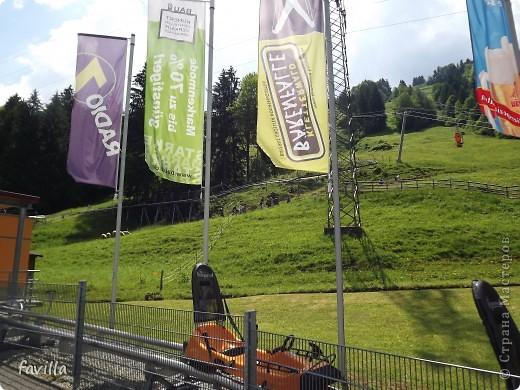 Alpsee Coaster самый длинный в Германии родельбан (горка для катания на санях) Длина 3 км, подъем в гору (на высоту около 1400 м) на подвесной дороге. При спуске - 68 поворотов, 23 волны, 7 прыжков, 4 моста, и 430-градусный спиральный поворот. Скорость развивается до 40 км в час Подъем в гору происходит на подвесной дороге.  Я фотографировала  маму и Вику со своего сиденья.  фото 21