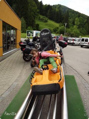 Alpsee Coaster самый длинный в Германии родельбан (горка для катания на санях) Длина 3 км, подъем в гору (на высоту около 1400 м) на подвесной дороге. При спуске - 68 поворотов, 23 волны, 7 прыжков, 4 моста, и 430-градусный спиральный поворот. Скорость развивается до 40 км в час Подъем в гору происходит на подвесной дороге.  Я фотографировала  маму и Вику со своего сиденья.  фото 24