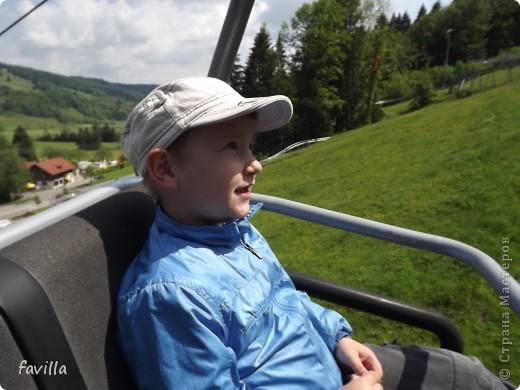 Alpsee Coaster самый длинный в Германии родельбан (горка для катания на санях) Длина 3 км, подъем в гору (на высоту около 1400 м) на подвесной дороге. При спуске - 68 поворотов, 23 волны, 7 прыжков, 4 моста, и 430-градусный спиральный поворот. Скорость развивается до 40 км в час Подъем в гору происходит на подвесной дороге.  Я фотографировала  маму и Вику со своего сиденья.  фото 25