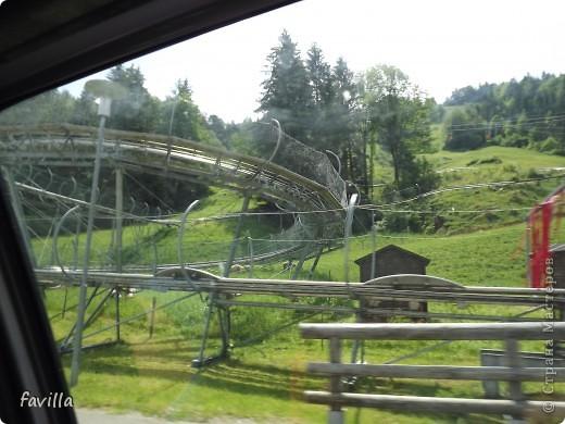 Alpsee Coaster самый длинный в Германии родельбан (горка для катания на санях) Длина 3 км, подъем в гору (на высоту около 1400 м) на подвесной дороге. При спуске - 68 поворотов, 23 волны, 7 прыжков, 4 моста, и 430-градусный спиральный поворот. Скорость развивается до 40 км в час Подъем в гору происходит на подвесной дороге.  Я фотографировала  маму и Вику со своего сиденья.  фото 33