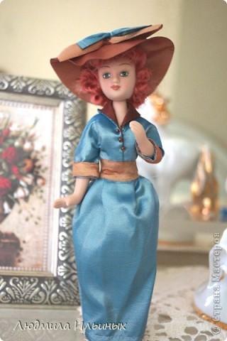 Для переделки этой куколки понадобилось несколько сантиметров атласной ленты коричневого и голубого цветов в тон платья и немного бисера. Заменила бант на шляпе и пояс, сшила сумочку, а так же чуть подправила форму губ. фото 1