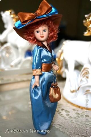 Для переделки этой куколки понадобилось несколько сантиметров атласной ленты коричневого и голубого цветов в тон платья и немного бисера. Заменила бант на шляпе и пояс, сшила сумочку, а так же чуть подправила форму губ. фото 4