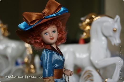 Для переделки этой куколки понадобилось несколько сантиметров атласной ленты коричневого и голубого цветов в тон платья и немного бисера. Заменила бант на шляпе и пояс, сшила сумочку, а так же чуть подправила форму губ. фото 12