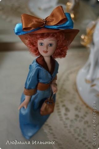 Для переделки этой куколки понадобилось несколько сантиметров атласной ленты коричневого и голубого цветов в тон платья и немного бисера. Заменила бант на шляпе и пояс, сшила сумочку, а так же чуть подправила форму губ. фото 13
