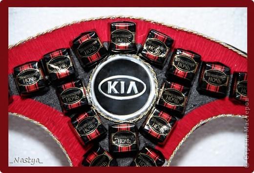 Подарок (вернее, дополнение к подарку - вместо букета) на день рождения молодому мужчине, который любит марку КИА и очень хочет заменить свою старую машину на новую. Это мой первый руль. Это - передок руля. На руль ушло около 1,5 кг конфет - 1 кг шоколадной ночи (59 конфет) и 0,5 кг - креамо с фендуком (32 конфеты). Сам руль из вырезан  пенопласта, обмотан атласной лентой и декорирован гофрой и золотой веревочкой. Скажу сразу - была бы в магазине черная гофра - сделала бы руль раза в три быстрее. Обматывать ленточками очень трудоемко, особенно в широких местах и на поверхности руля. фото 5