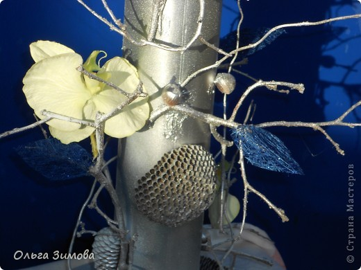 Вот такую напольную вазу я сделала своей близкой родственнице. Девушка с фантазией, поэтому надеюсь она будет довольна подарком.За  основу взяла пластмассовую трубу, декорировала сухими веточками айвы Украсила орешками- фундуком, шишками..Покрасила серебром из баллончика. Немного подработала белым цветом.И в заключении украсила искусственными цветами и листочками из сизаля. фото 2