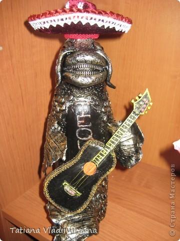 Это бутылка . Снимаем шляпу и внутри пробка. Самоотвердевающая пластика, акриловые краски. Гитара сделана из бумаги. Шляпа из баночки от краски, поля из пластика от бутылки. Обтянута бархатом, украшена кружевами. Бутылка сделана на заказ в подарок настоящему мексиканцу проживающему в Москве.  фото 1