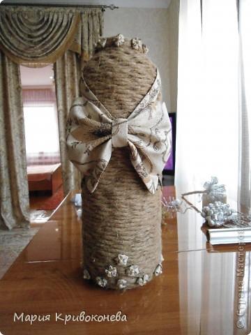 """Идею этой вазы я нашла в журнале """"1000 советов"""". Эта ваза выполнена из двух трехлитровых банок, склееных друг с другом. Место стыка я закрыла обложкой какого-то журнала. Далее проклеила всю поверхность газетой (на ПВА). В магазине я нашла тройной канат, раскрутила его и обмотала все снизу вверх (поэтому поверхность немного волнушками). Украшением послужил бант из остатков штор (кстати они на заднем плане) и мелкие цветочки из той же ткани с бусинками. фото 1"""