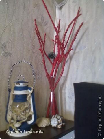 Ветки и растопленная свеча красного цвета. фото 1